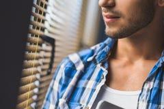Barba de un hombre joven que está mirando en la ventana Foto de archivo