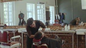 Barba del corte del peluquero con las tijeras en la barbería metrajes