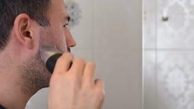 Barba della guarnizione dell'uomo sullo specchio in bagno stock footage