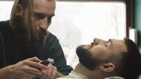 Barba do corte da mão do barbeiro com a tosquiadeira no barbeiro O barbeiro trabalha com o ajustador bonde vídeos de arquivo