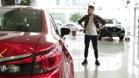 Barba masculina del frotamiento del cliente que elige cuidadosamente un nuevo coche en la representación almacen de metraje de vídeo
