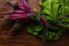 Barbabietola rossa con le foglie verdi delle erbe su fondo rustico Barbabietole organiche detox immagine stock