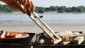 Barbacoa - asando a la parrilla las salchichas y el queso de soja en una playa del río - 4k almacen de video