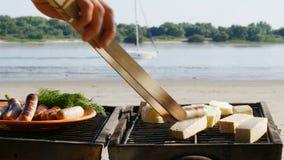 Barbacoa - asando a la parrilla las salchichas y el queso de soja en una playa del río - 4k metrajes