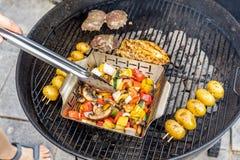 Barbacoa con la carne y las verduras en una terraza foto de archivo
