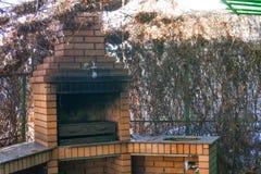 Barbacoa de la chimenea en una cerca viva en otoño imagen de archivo libre de regalías