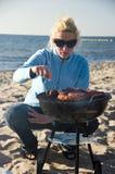 Barbacoa de la mujer y de la playa Foto de archivo libre de regalías