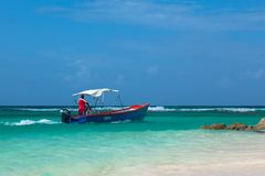 Barbadian men in red skirt on blue boat in azure water of Caribbean sea. Worthing beach. stock images