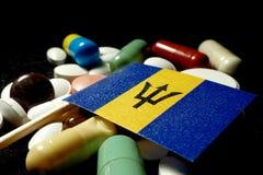 Barbadische Flagge mit Los medizinischen Pillen lokalisiert auf schwarzem backg Lizenzfreies Stockbild