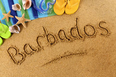 Barbados beach writing. The word Barbados written on a sandy beach, with scuba mask, beach towel, starfish and flip flops Stock Images