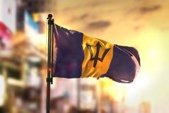 Barbados flagga mot suddig bakgrund för stad på soluppgång Backlig Royaltyfri Foto