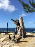 Barbados Ocean view scene with old anchor. Barbados Ocean view scene with blue skies and hint of a tree with an old anchor leaning against old tree stump Stock Image