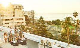 Barbaque del tejado en la puesta del sol con el grupo de adultos jovenes atractivos Fotos de archivo libres de regalías