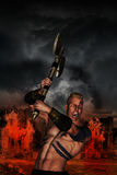 Barbarian warrior with flaming village. Storming clouds on the sky Stock Photos