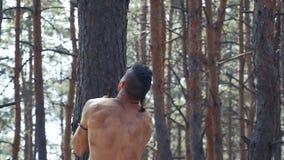 Barbarzyńcy wojownik rzuca jego cioski na ziemi i wspina się na drzewie zbiory