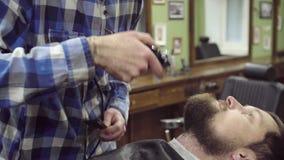 Barbe de règlage de femme de coiffeur de client avec la tondeuse au raseur-coiffeur banque de vidéos