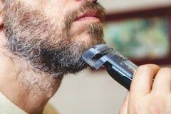 Barbe de toilettage avec le plan rapproché gris de trimmer de cheveux photo libre de droits