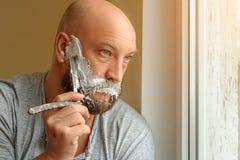 Barbeações farpadas de um homem com uma lâmina reta fotos de stock
