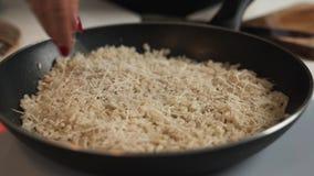 Barbeando bocados do queijo parmesão no risoto quente em uma grande bandeja de aço inoxidável, fim acima do vídeo vídeos de arquivo