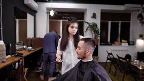 Barbearia de visita do moderno do homem Barbeiro da mulher que faz o corte de cabelo à moda Ideia do interior da barbearia filme