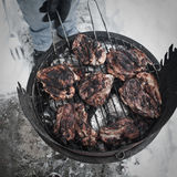 Barbecue. Grilling meat outside on a snowy day Stock Photos