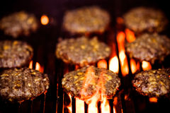 Barbecue. Hamburger with cheese on the grill under flame Royalty Free Stock Photos