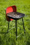 Barbecue. Red grill standing on green grass Royalty Free Stock Photography