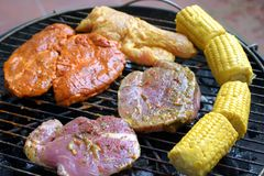 Barbecue. Marinated meat and corncobs on a hot barbecue grill royalty free stock image