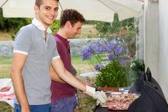 Barbecue avec des amis dans le jardin, cuisson de deux garçons Image libre de droits