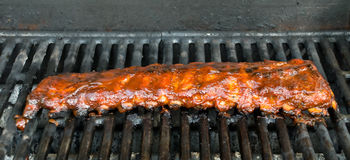 Barbecue Baby Back Ribs. Cooking on a BBQ Grill Royalty Free Stock Image