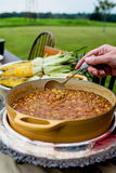 Barbecue Beans Being Served at Outdoor Dinner Party. BBQ beans being served at a rustic outdoor fall dinner party Stock Image