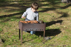 Barbecue. The boy fries meat on a brazier Royalty Free Stock Photo