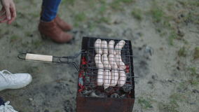 Barbecue browned sausages on the hot grill, a person turn and put upon brazier closeup stock video footage