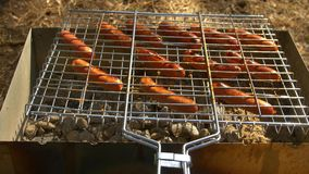 Barbecue browned sausages on the hot grill, turn. Barbecue browned sausages on the hot grill, a person turn and put upon brazier stock video footage
