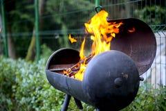 Barbecue bruciante di legno in cortile Immagini Stock