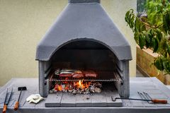 Barbecue in built barbecue grill fireplace with fish and chevaps. Concrete bbq fireplace back yard fireplace in Croatia stock photo