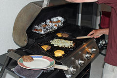 Barbecue with burgers. And sausages Stock Images