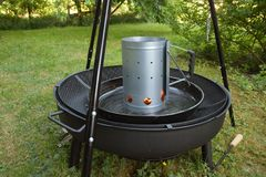 Barbecue charcoal chimney starter on a black tripod swivel grill. In the garden royalty free stock image
