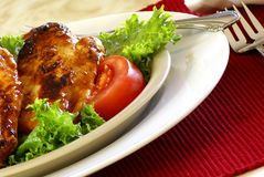 Barbecue Chicken. Grilled boneless chicken breast with bbq sauce, salad greens and tomatoes Royalty Free Stock Photography