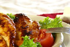 Barbecue Chicken. Grilled boneless chicken breast with bbq sauce, salad greens and tomatoes Royalty Free Stock Photos