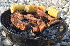 Barbecue chicken cooking on the beach with sweet corn royalty free stock photography