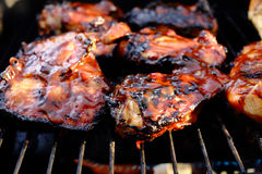 Barbecue chicken on grill. Several pieces of chicken on barbecue grill coated in barbecue sauce Stock Photos