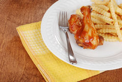 Barbecue chicken legs with fries and yellow napkin Royalty Free Stock Photo