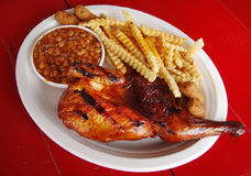 Barbecue Chicken Plate. A plate of southern barbecue chicken with baked beans, hush puppies, and french fries Stock Photo