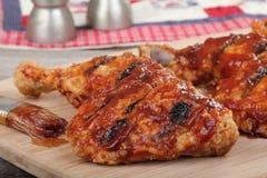 Barbecue Chicken Quarters Closeup. Closeup of barbecue chicken quarters on a cutting board Stock Photos