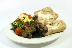 Barbecue chicken and sides. White plate filled with barbecued chicken, bread roll, and salad, with white background Stock Photo