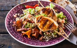 Barbecue chicken skewer dish with quinoa close up. A close up of a healthy, gourmet barbecue chicken skewer dish and utensils with quinoa, mushrooms, chilli and royalty free stock photos
