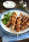 Barbecue chicken skewers with yogurt sauce. Barbecue chicken skewers with yogurt sauce on wooden table Stock Photos