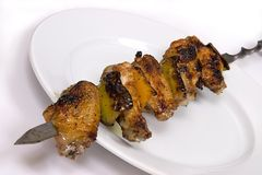 Barbecue chicken wings. On spit and white dish. Kebab on a white background Stock Images