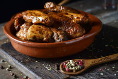 Barbecue chicken wings. Closeup of some barbecue chicken wings in an earthenware plate on a rustic wooden table stock images